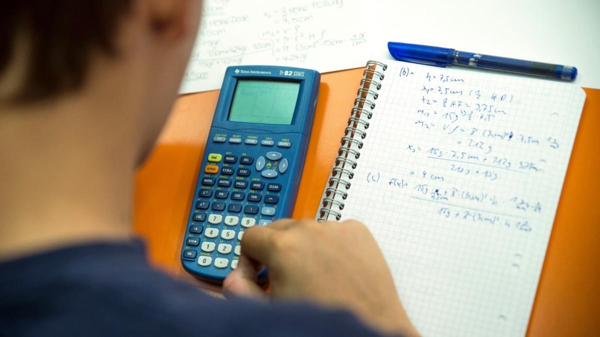 Ein Student gibt etwas in seinen Taschenrechner ein.