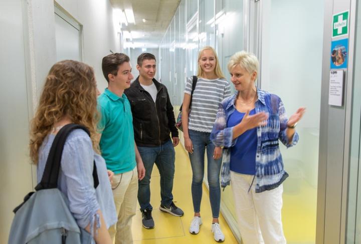 Eine Beraterin der Zentralen Studienberatung begrüßt Studierende vor einem Termin. (c)