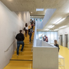 Young people climbing the stairs in the House of Students of the University of Stuttgart.