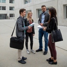 Four students talking in front of the House of Students at the University of Stuttgart.